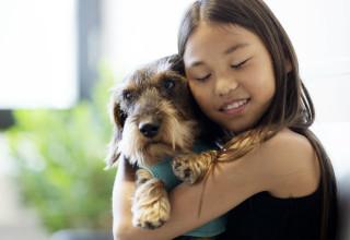 Petite fille serrant son chien contre elle