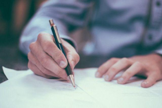 Fotographie eines Mannes bei der Unterzeichnung eines Vertrages.