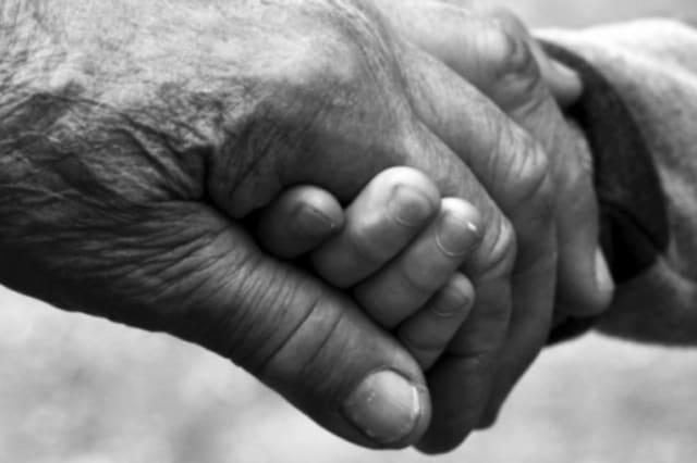 Ein alter und ein junger Mensch geben sich gegenseitig die Hand.