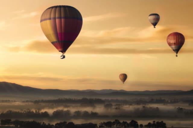 Fotographie von Heißluftballons in der Morgenröte.