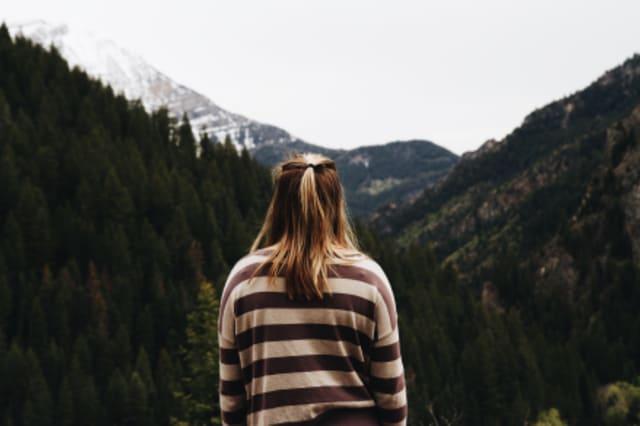 Fotographie einer Frau vor einem Bergpanorama.