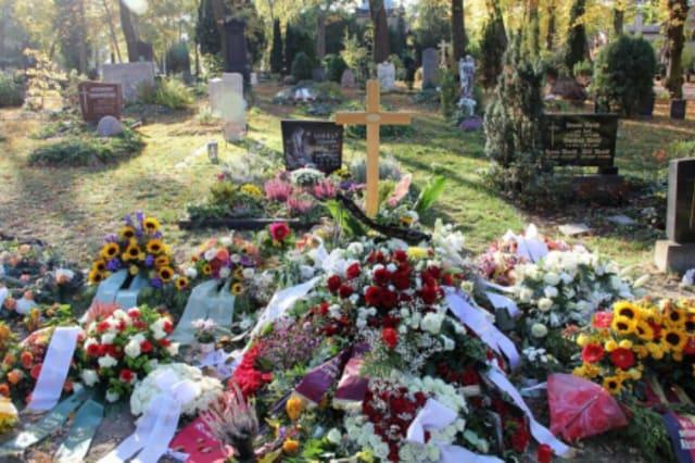 Fotographie eines frischen Grabes mit Blumenkränzen und Holzkreuz.