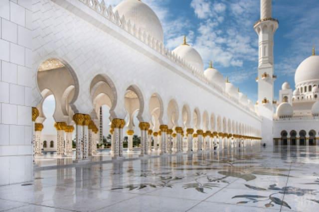 Fotographie einer weißen Mosche mit Minarett im Hintergrund.