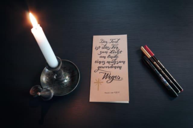 Fotographie einer Kerze neben einer Todesanzeige mit drei Stiften.