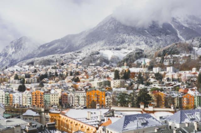 Panoramaaufnahme von Innsbruck, mit Bergen im Hintergrund.