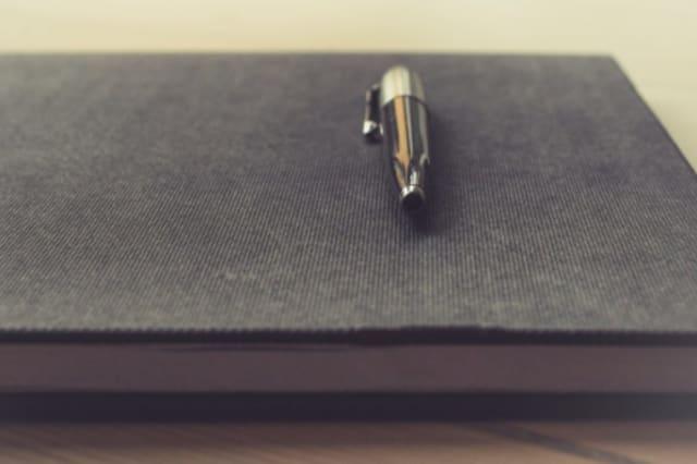 Fotographie eines Kugelschreibers auf einem geschlossenen Notizbuch.