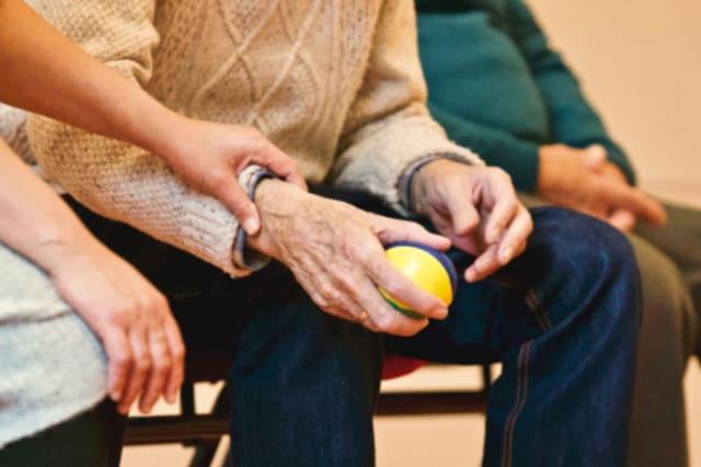 Fotographie eines älteren Mannes mit einem Ball in der Hand, welcher von einer Pflegerin unterstützt wird.