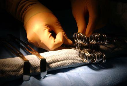 Fotographie der Hände eines Operateurs beim Vorbereiten der OP Instrumente.