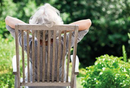Fotographie einer älteren Dame, welche sich entspannt in ihrem Gartensessel zurücklehnt.