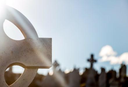 Fotographie eines Kreuzes am Friedhof im Sonnenschein.