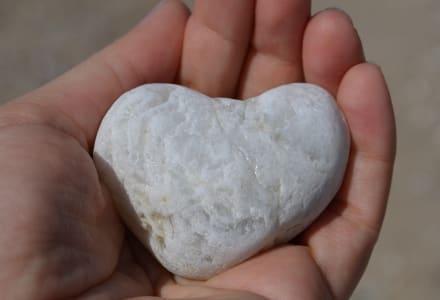 Fotographie eines herzförmigen Steines in einer Handfläche.