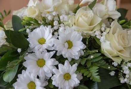 Fotographie eines Blumengestecks bei einer Trauerfeier.