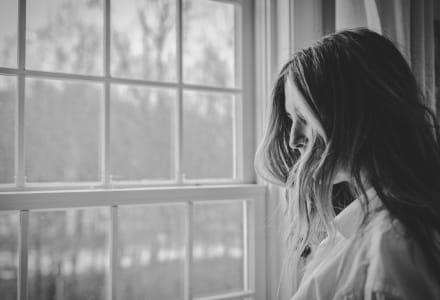 Schwarz-Weiß-Fotographie einer trauernden Frau am Fenster.