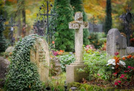 Fotographie verwitterter Grabstellen auf einem alten Friedhof.