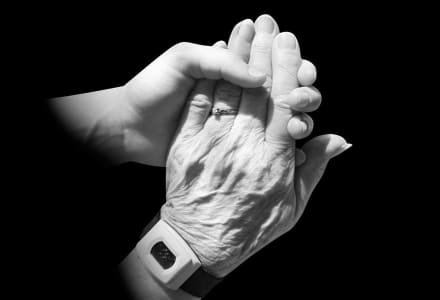 Schwarz-Weiß-Fotographie einer jungen Hand, die die Hand einer älteren Person greift.
