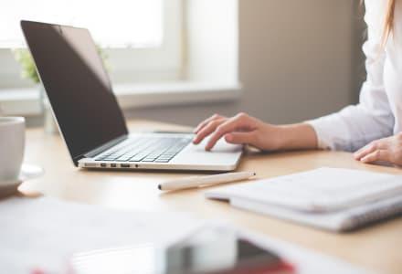 Fotographie einer Frau, die an ihrem Laptop arbeitet.