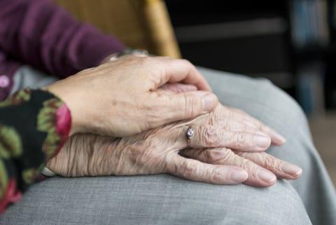 Eine junge Hand liegt tröstend auf einer älteren Hand.