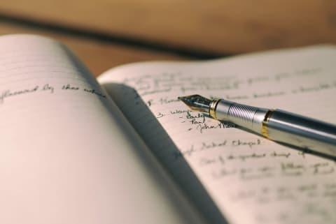 Fotographie eines offenen Notizbuches mit Füllfeder.