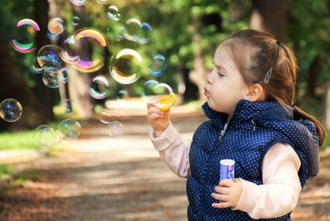 Fotographie eines kleinen Mädchens beim Spielen mit Seifenblasen.