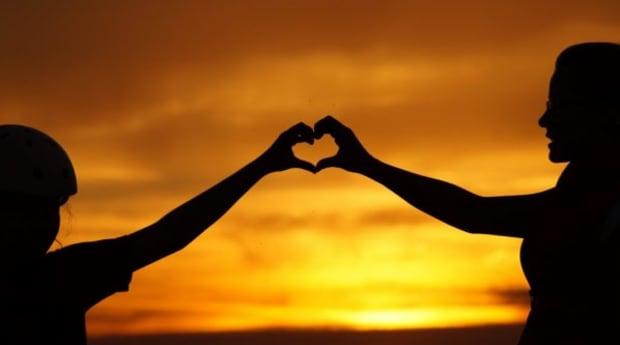 Herz aus zwei Händen im Sonnenuntergang