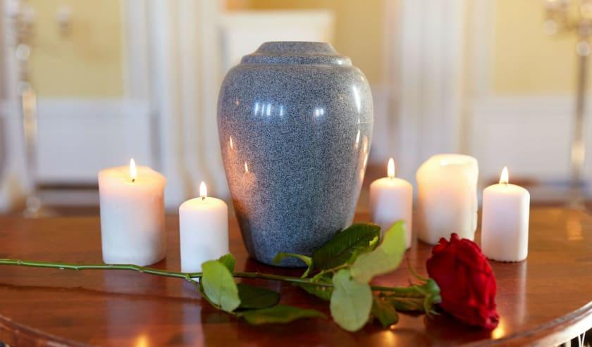 Arrangement von Urne, Rose und Kerzen.