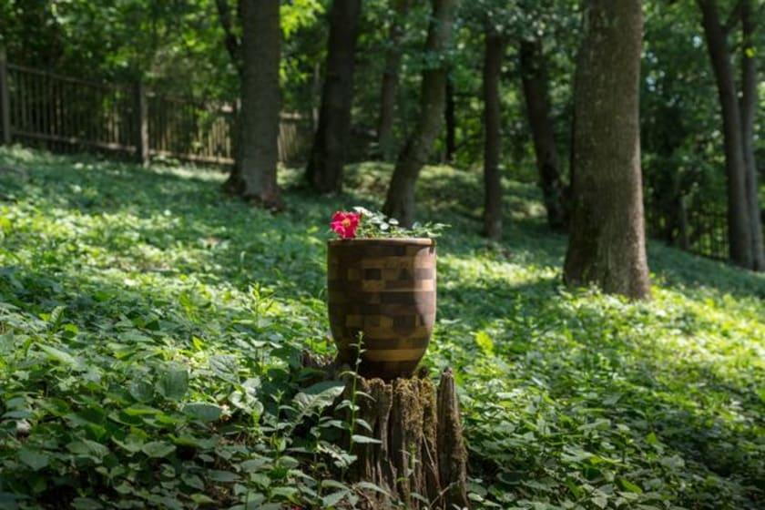 Fotographie einer Urne bei einer Trauerfeier im Wald.