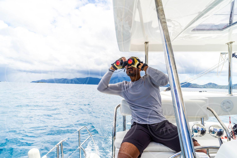 Man at helm of sailboat looking through binoculars