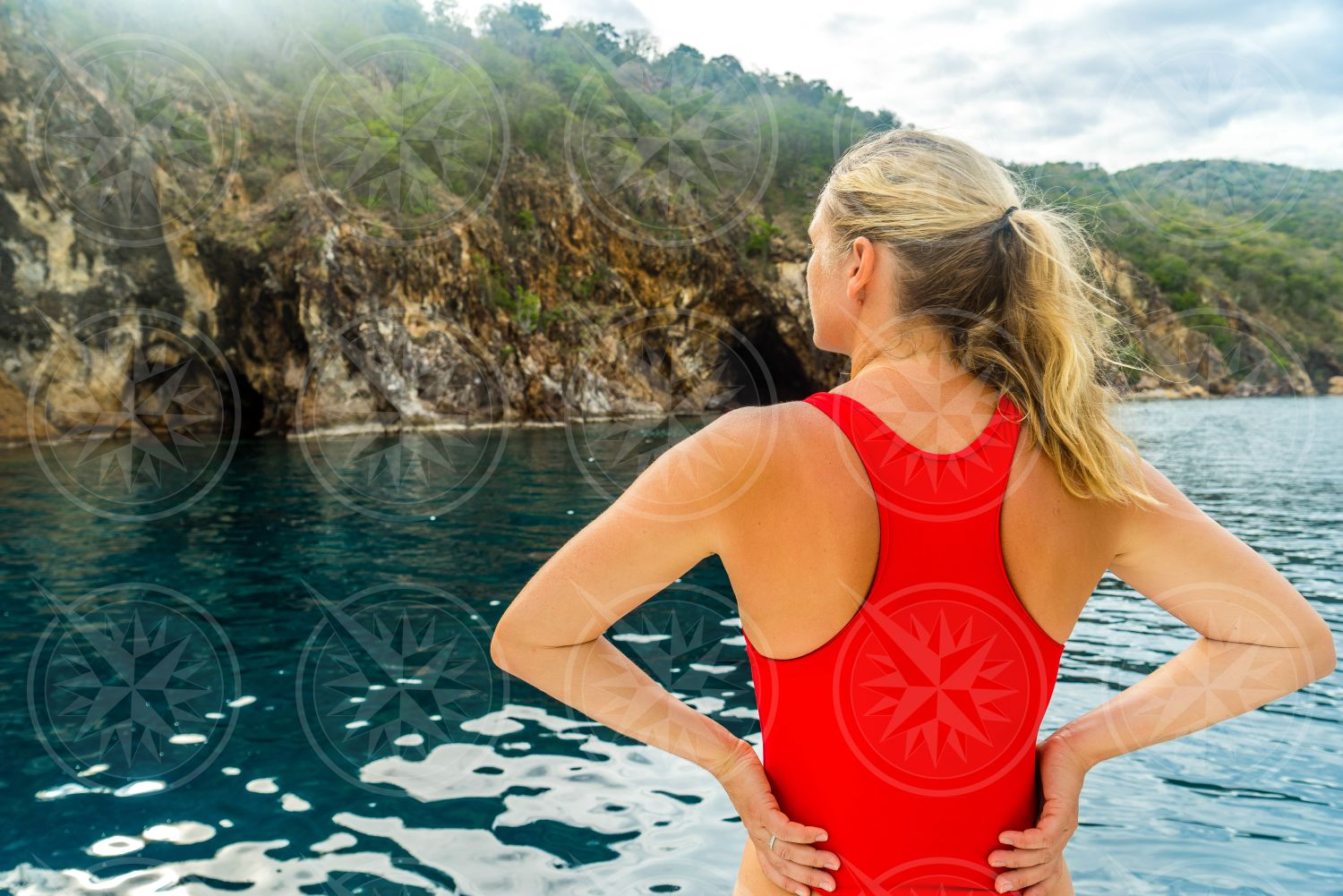 Woman in red swimsuit looking at Treasure Point Caves
