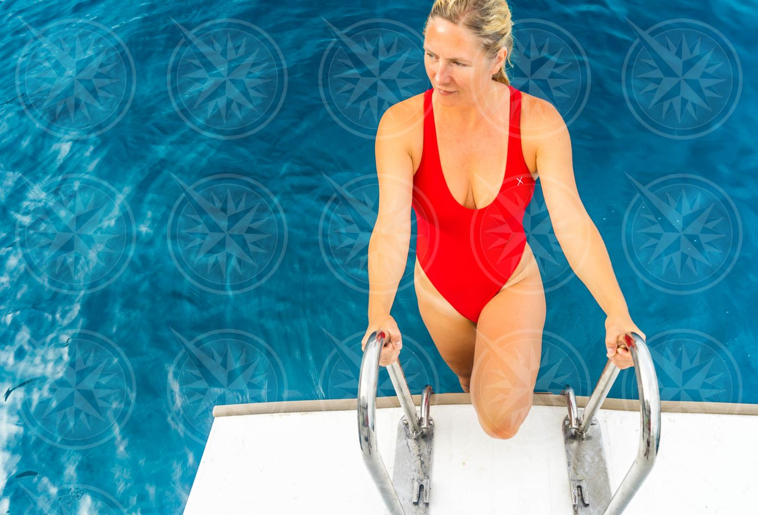 Woman in red swimsuit climbing swim ladder