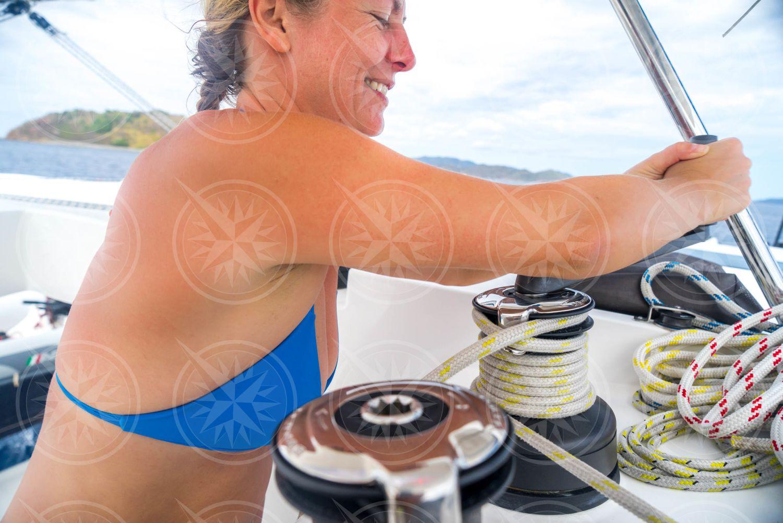 Woman in blue bikini grinding winch on sailboat