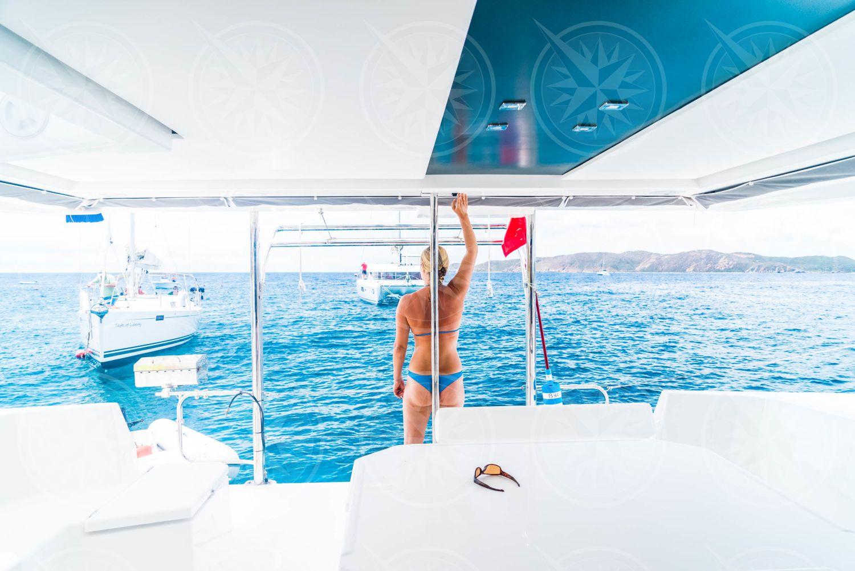 Woman in bikini operating sailboat davit