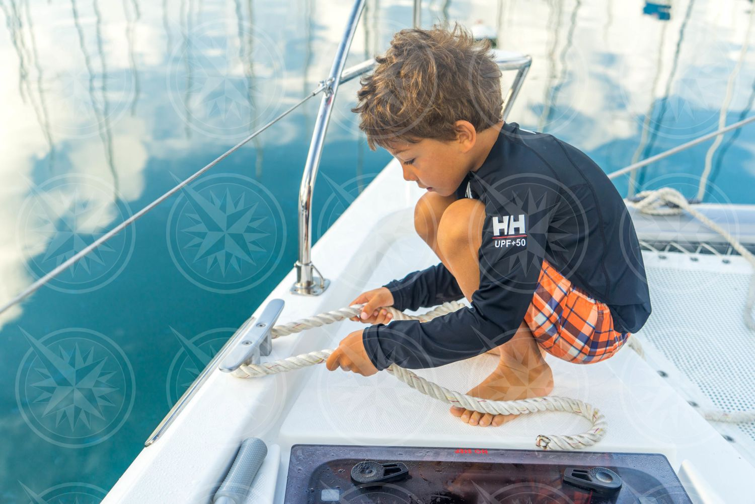 Young boy tying dock line