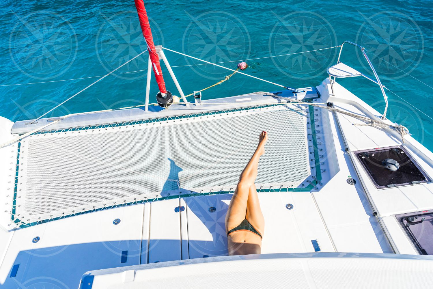Woman laying near bow of catamaran from above
