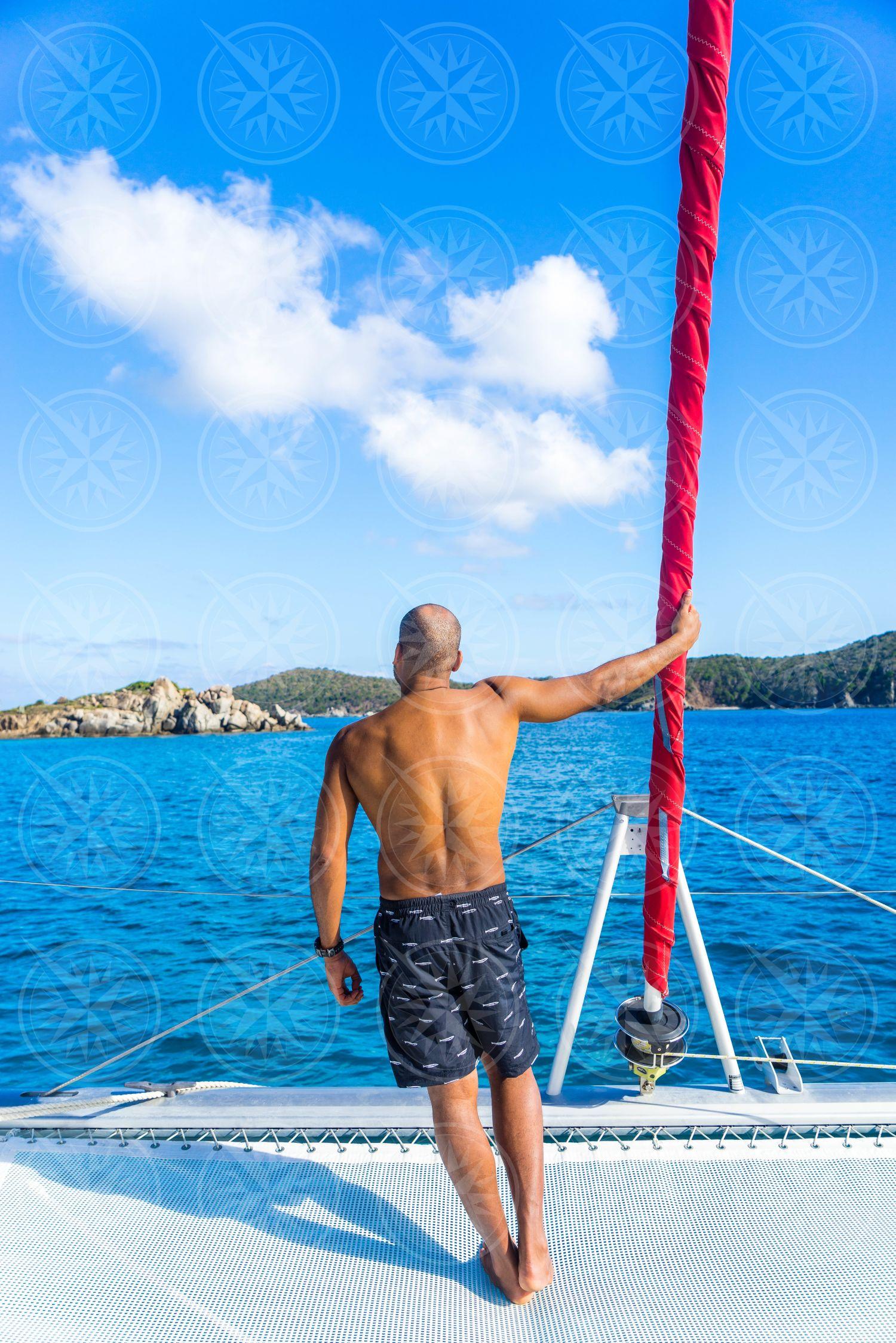 Man holding jib at bow of catamaran