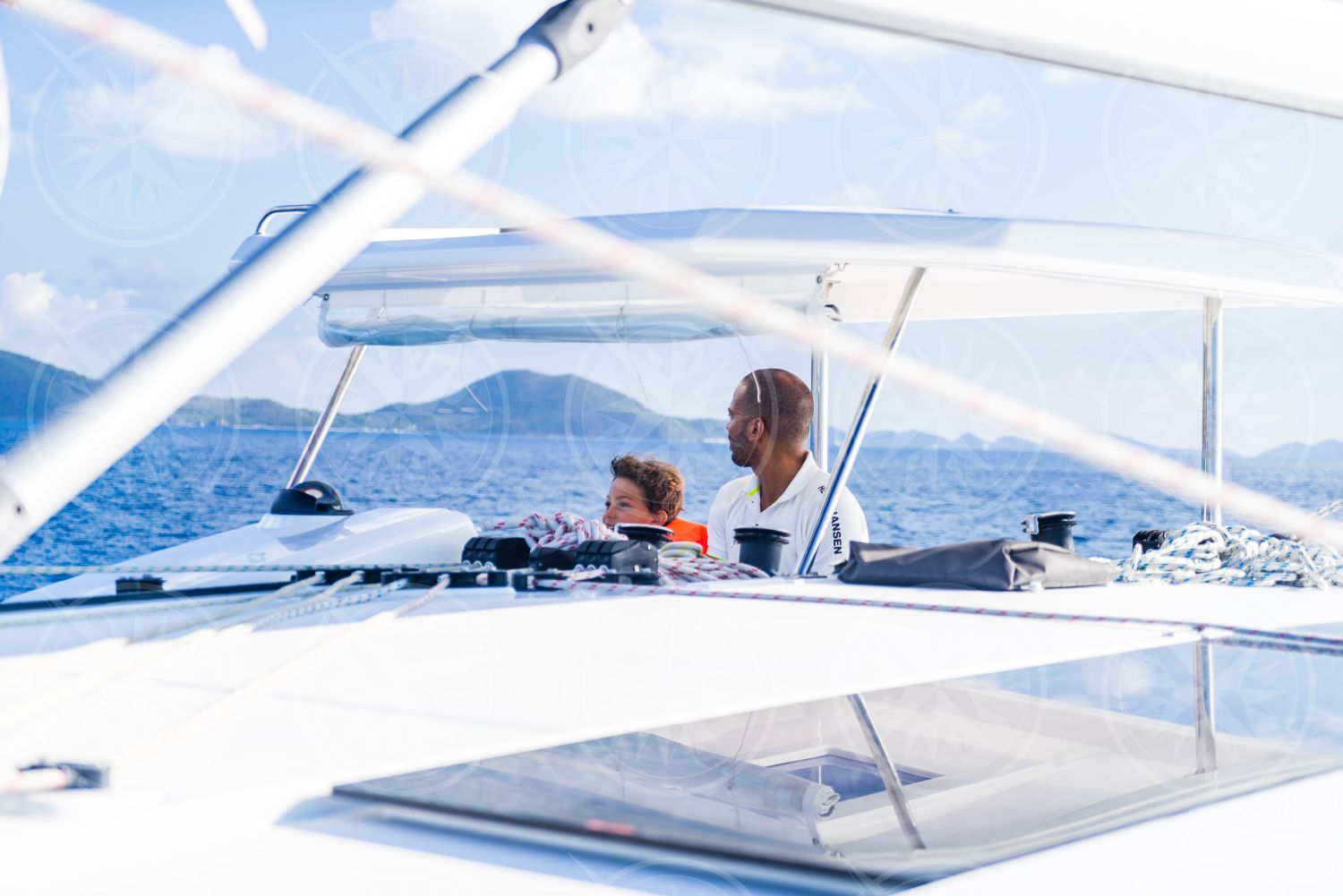 Man and boy at the helm of sailboat