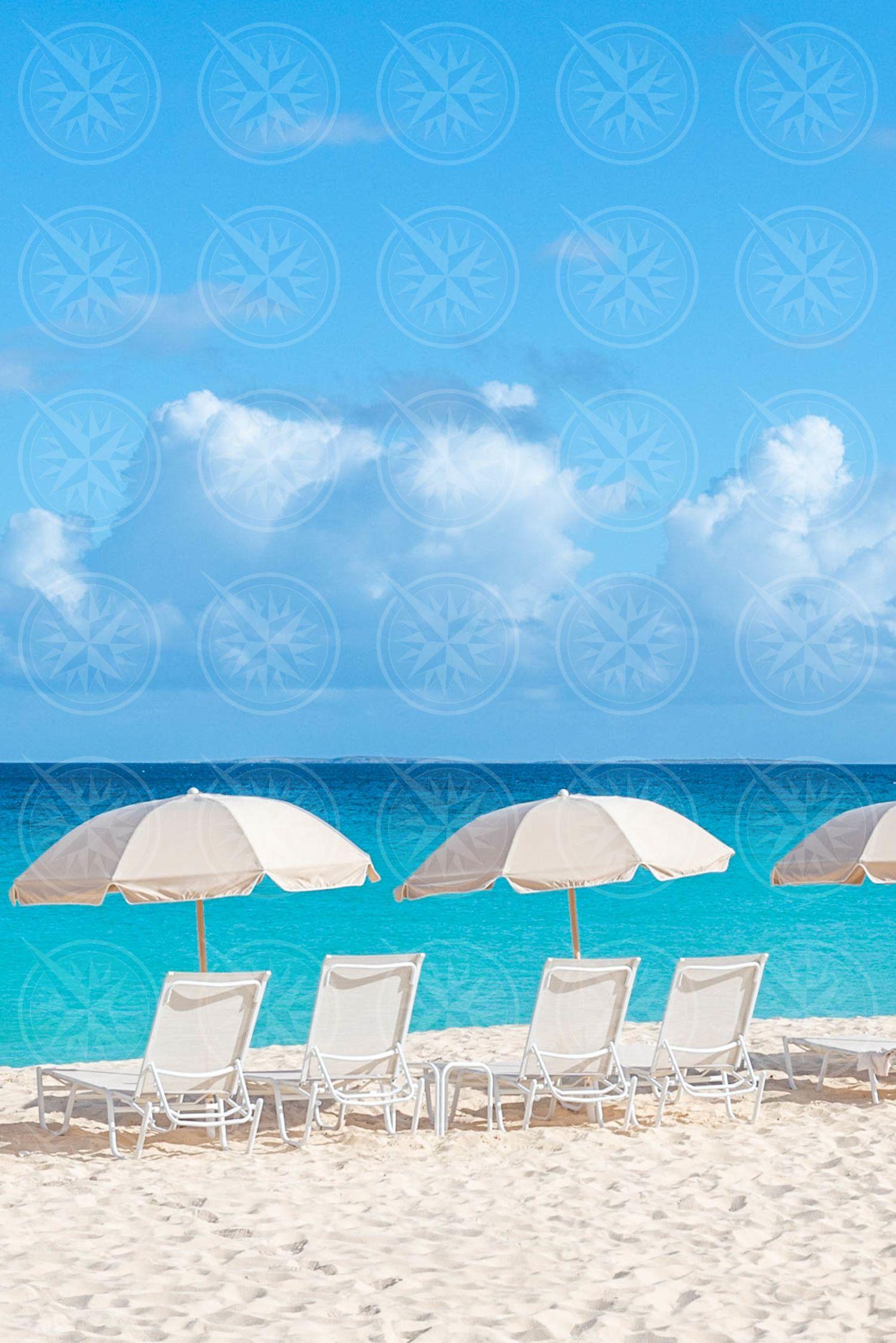 Line of umbrellas on white sand beach