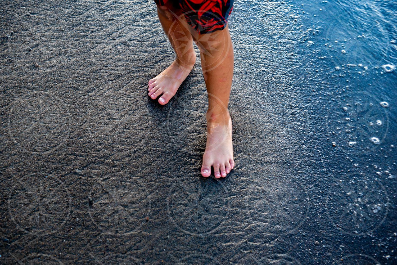 Boy on black sand beach