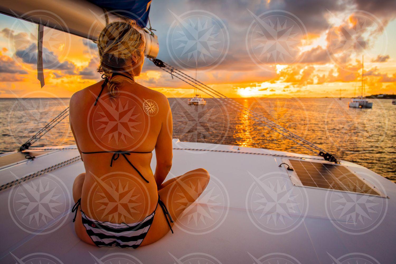 Woman on sailboat at sunset