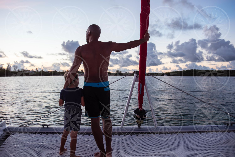 Man and boy on sailboat at sunset