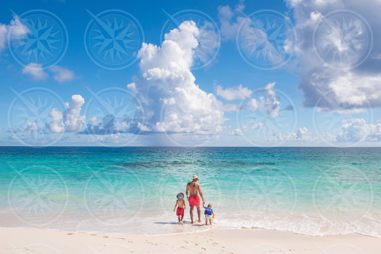 Man with two kids on white sand beach