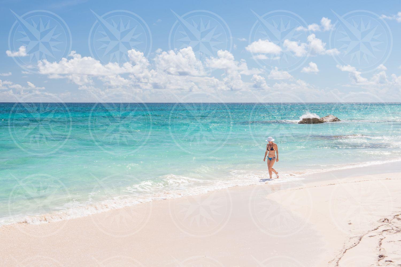 Woman in bikini on white sand beach