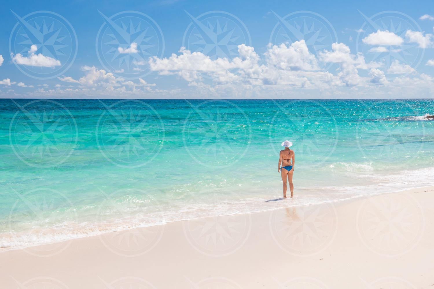 Woman in bikini on white sand beach