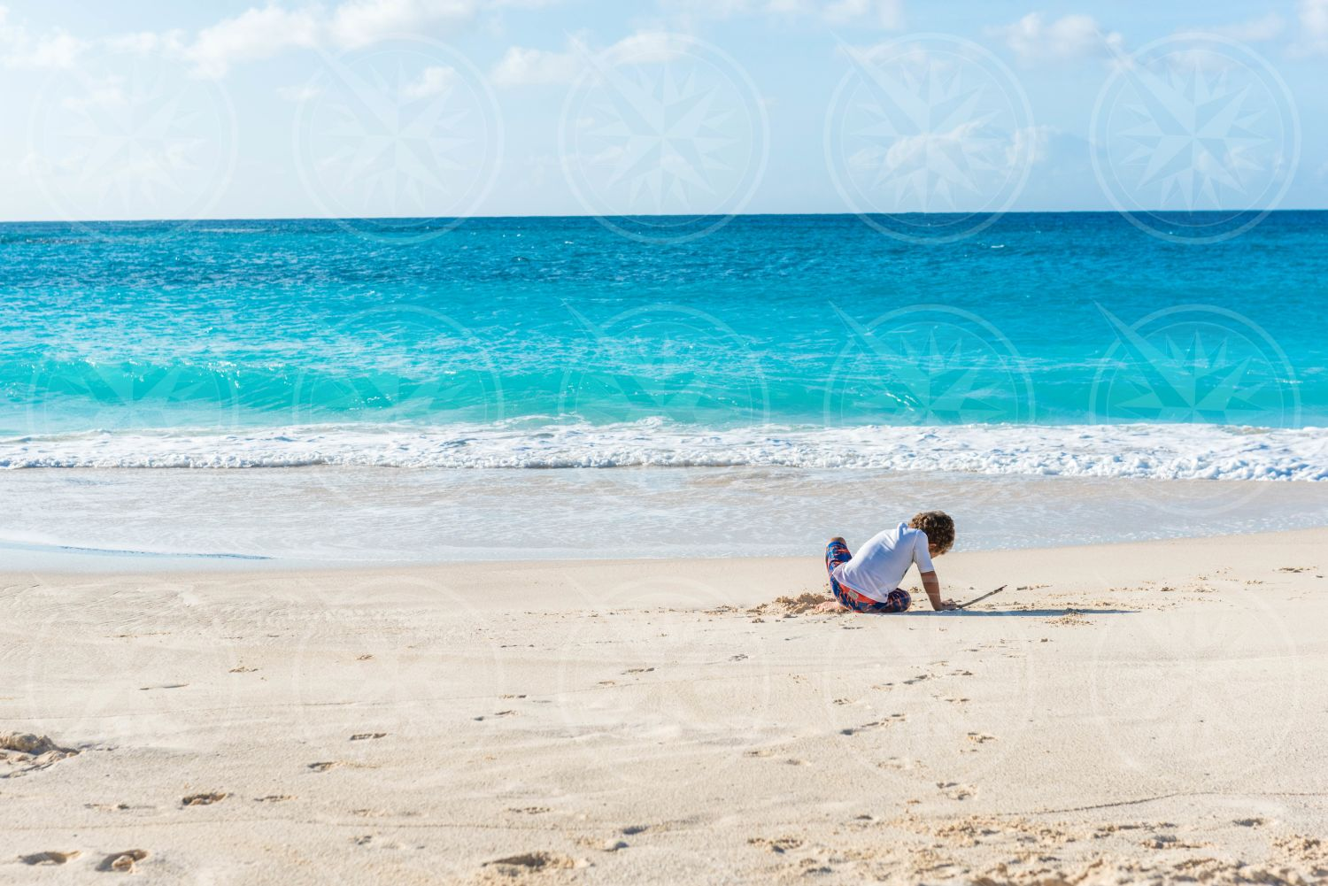 Young boy playing on white sand beach