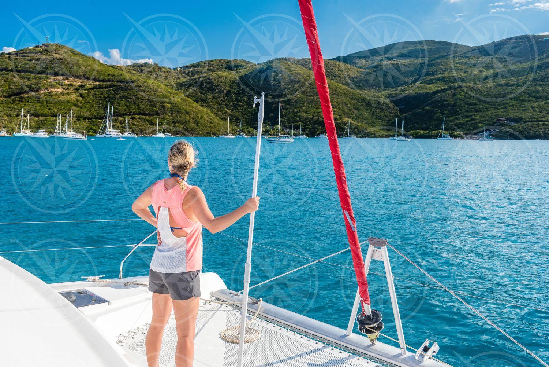 Woman at bow of catamaran ready to pull a mooring