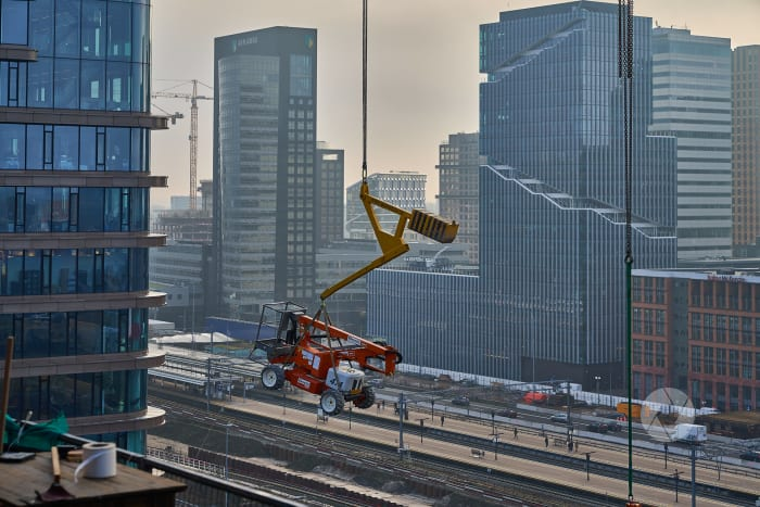 een hoogwerker wordt via bouwkraan verplaatst