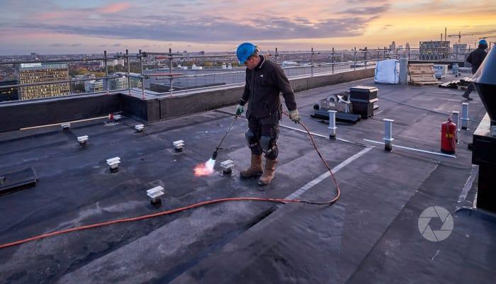 Zuidas, Xavier: Bitumen aanbrengen op dak van hoogste etage.