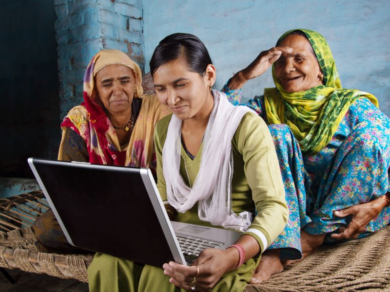Women in India gather around a laptop. Image: iStock