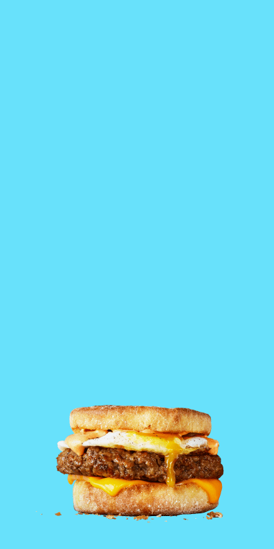 Impossible sausage food items stacked on top of one another on blue background