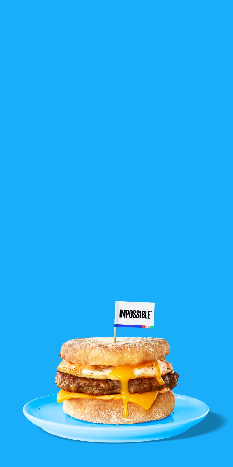 An Impossible Sausage breakfast sandwich dripping with egg and cheese on a blue plate and blue background