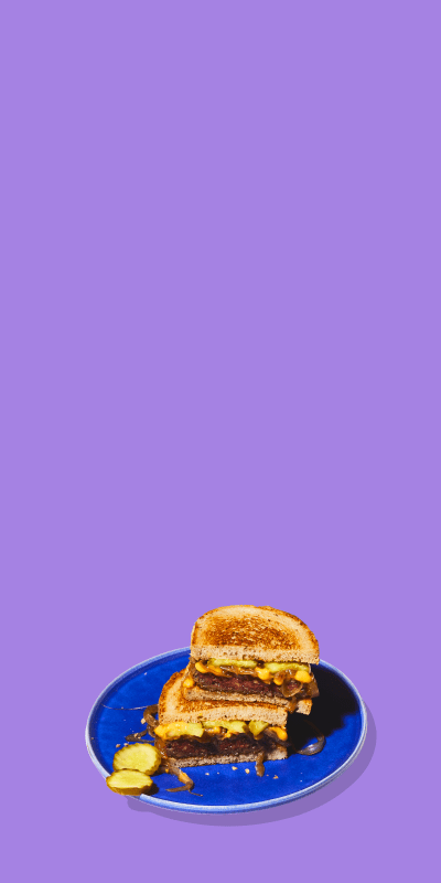 Impossible Burger Patty Melts on plates on purple background